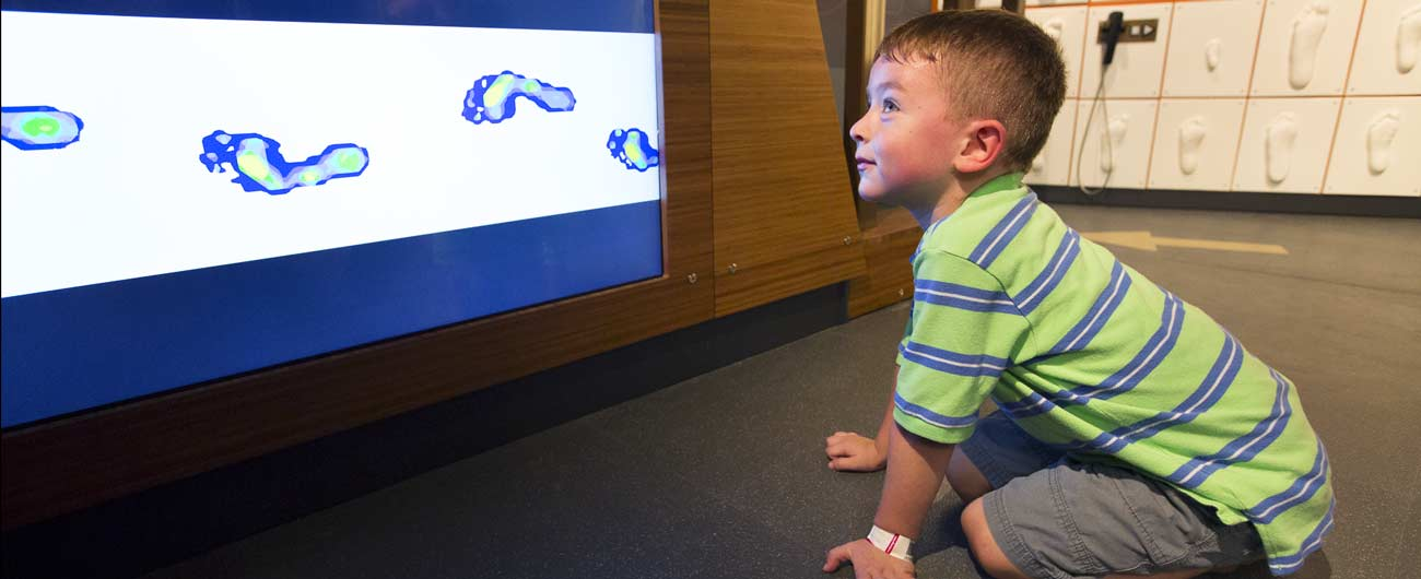 A young boy looks at images of feet on a screen
