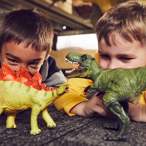Two young boys play with toy dinosaurs