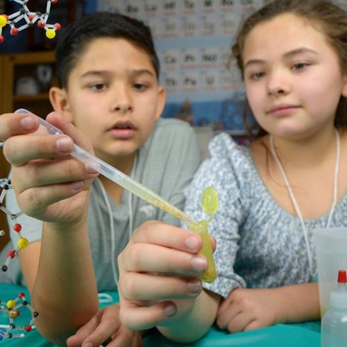 Boy and girl handle pipette and test tube