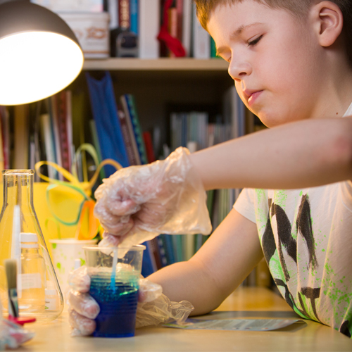 Young boy with gloves mixing blue liquid in a cup on a table