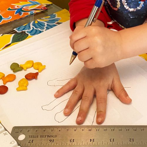 Boy tracing hand for measuring activity