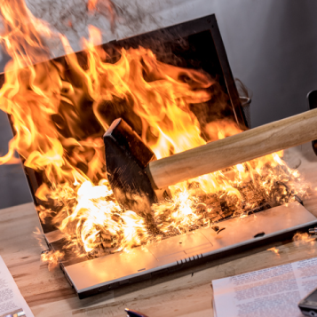 A laptop that is on fire and being hit with a bat