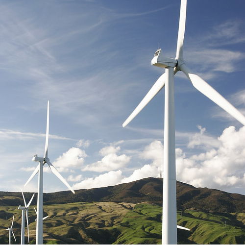 White windmills in front of a landscape of a green hill