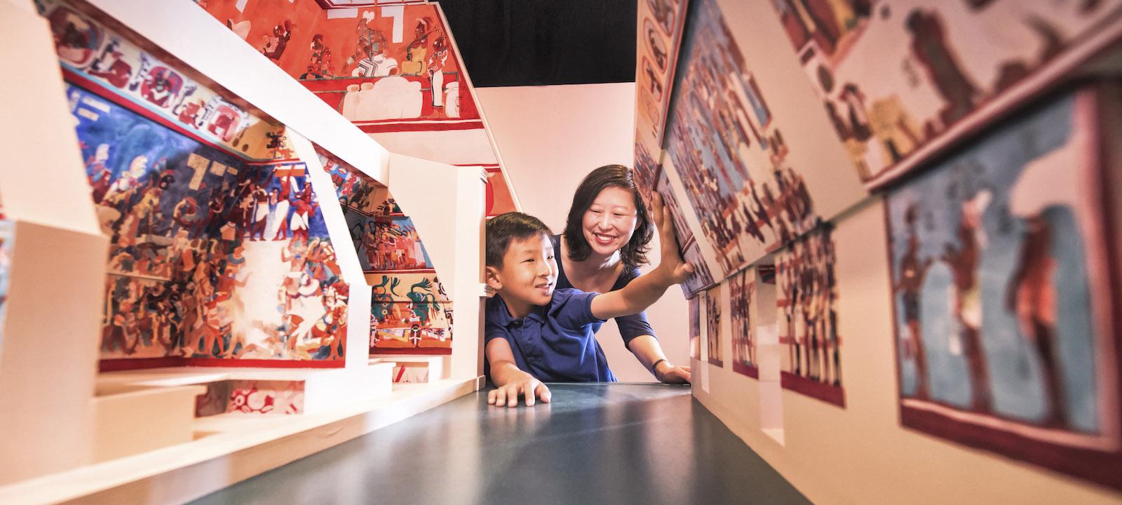 Mother and son exploring the bonampak mural room